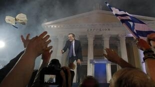 Leader of the New Democracy conservative party Antonis Samaras throws flowers to his supporters
