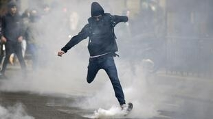 A youth kicks a teargas cannister during the protest in Paris