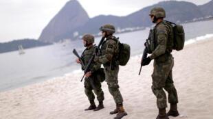 Forças armadas na praia do Flamengo, no Rio de Janeiro, 19 de julho, durante Jogos olímpicos, sucesso desportivo, mas com violência nas favelas