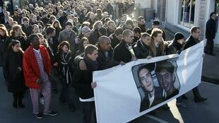 Des amis d'Antoine de Léocour et Vincent Delory portent une banderole aux portraits des deux otages décédés, durant la marche en leur mémoire, à Linselles, le 16 janvier 2011.