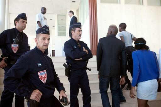 Relations of the accused pass by riot police at the trial in Pontoise