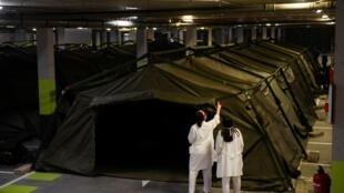 Des membres des Unités militaires d'urgence déploient des tentes dans le parking du CHU d'Asturias, le 19 mars 2020.