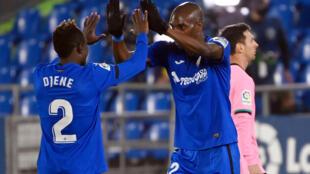 Les défenseurs de Getafe, le Togolais Djene Dakonam (g) et le Camerounais Allan Nyom, fêtent leur victoire non loin de l'attaquant argentin de Barcelone, Lionel Messi (d), à l'issue du match de Liga à Getafe, le 17 octobre 2020