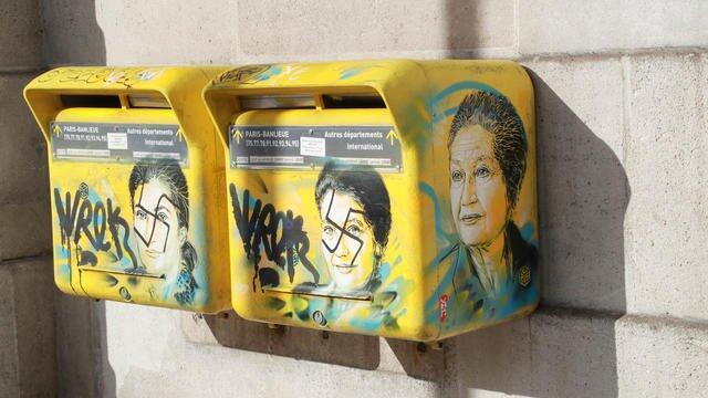 Caixas do correio vandalizadas com a cruz soática sobre a fotografia de Simone Veil