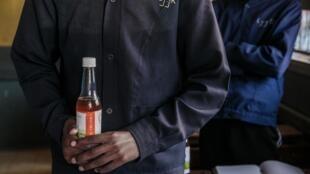 Un étudiant malgache tient une bouteille de Covid-Organics, présenté par le président Andry Rajoelina comme un puissant remède au Covid-19.