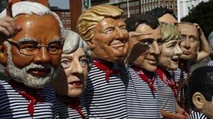 Activistas de la ONG Oxfam con máscaras de los líderes del G20 en una manifestación en Hamburgo durante la cumbre, el 6 de julio de 2017.