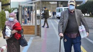 Des personnes portant des masques à la sortie de l'hôpital El-Kettar dans la capitale algérienne Alger, le 26 février 2020.