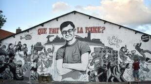 "A mural in Nantes, western France, depicting Steve Canico, whose body was discovered in the Loire river more than a month after he disappeared during a police intervention at a music festival. At top the mural reads, ""What are the police doing?"""