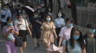 Unos transeúntes con mascarilla se dirigen al trabajo el 28 de junio de 2020 en Pekín