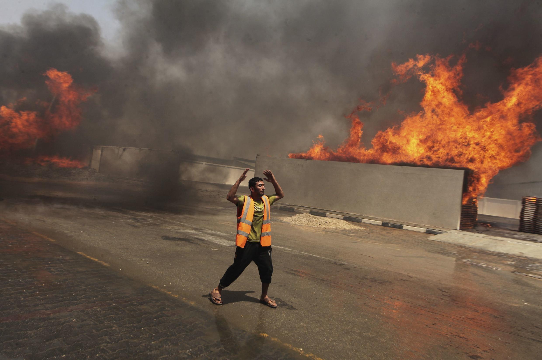 Một người Palestine tại dải Gaza gọi cứu hỏa sau khi bị oanh kích ngày 12/07/2014.