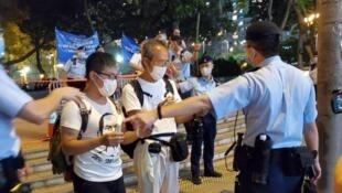 黃浩銘(左)和徐漢光被警方攔截,在維園外就地點燭和高唱民運歌