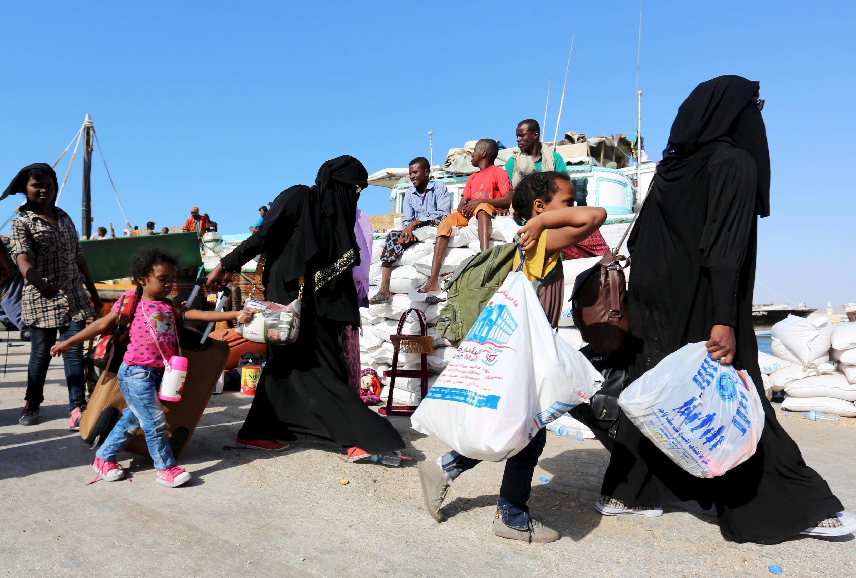 Uma família iemenita que foge da violência no Iêmen leva seus pertences enquanto desembarca um navio no porto de Bosasso, na região de Puntland, na Somália, em 16 de abril de 2015.