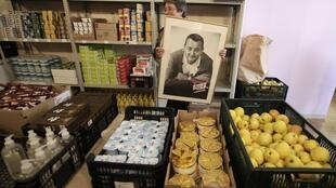 A restaurant for the poor in France with a photo of comedian Coluche who founded the Restos du coeur