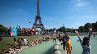 Des Français se rafraîchissent aux abords de la Tour Eiffel, le 2 août 2018, en plein coeur d'une vague de chaleur qui frappe l'Europe.