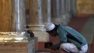 Homem lê o Alcorão, livro sagrado dos muçulmanos, em mesquita na cidade do Cairo.