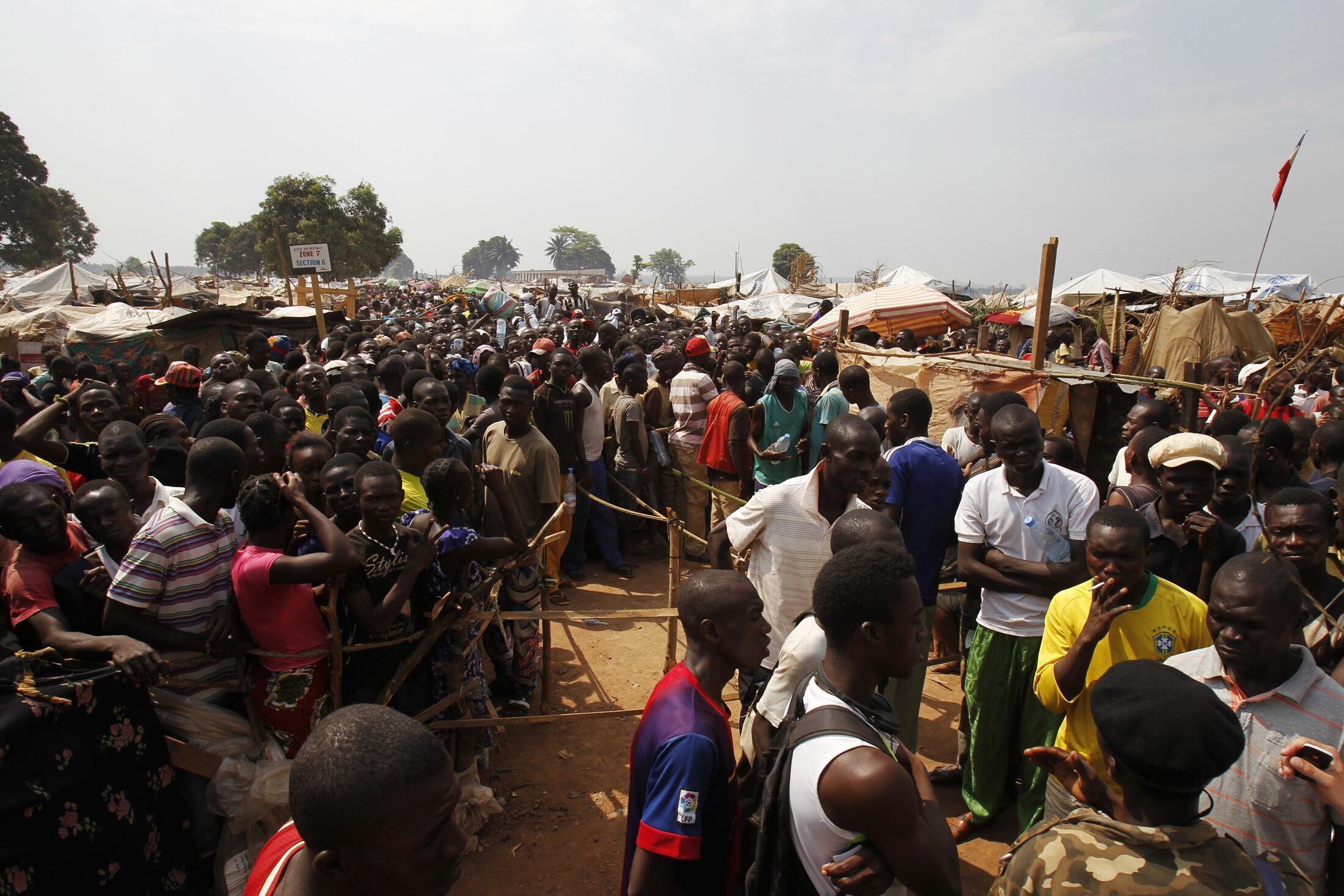 Des déplacés attendant de la nourriture dans un camp près de l'aéroport international Mpoko de Bangui, le 12 février 2014.