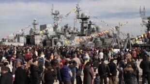 Celebraciones populares en el día de defensa de la patria, con navíos de guerra rusos de fondo, Sebastopol, Crimea, 23 de febrero de 2015.