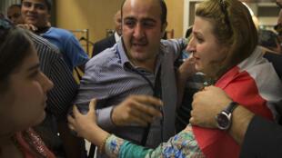 Des réfugiés chrétiens irakiens retrouvent leur famille à leur arrivée à Paris, le 21 août 2014.