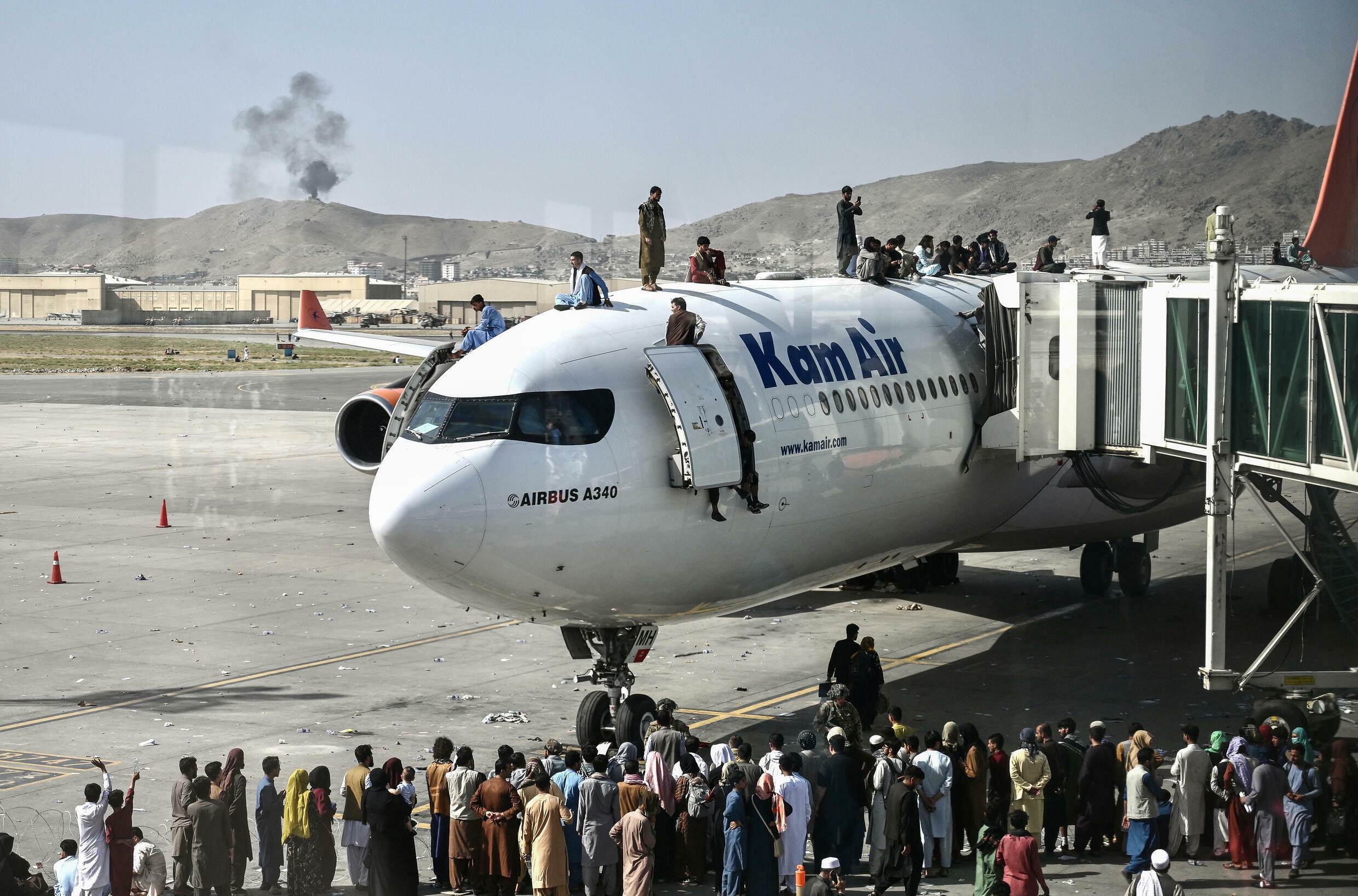 Afghan people climb atop a plane as they wait at the Kabul airport after a stunningly swift end to Afghanistan's 20-year war, as thousands of people mobbed the city's airport trying to flee the group's feared hardline brand of Islamist rule