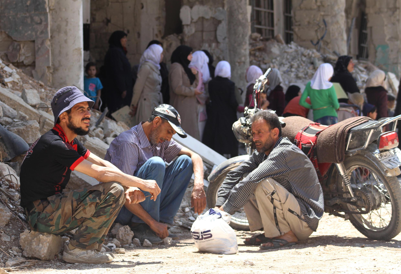 Sírios sentados ao lado de um edifício danificado na cidade de Daraya, sudoeste de Damasco, em 23 de Maio de 2016.
