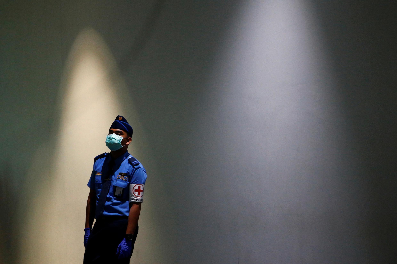 Un agent de la sécurité de l'aviation attend l'arrivée de passagers dans l'aéroport international de Jakarta, après la confirmation d'un premier cas de coronavirus en Indonésie, le 6 mars 2020 (photo d'illustration).