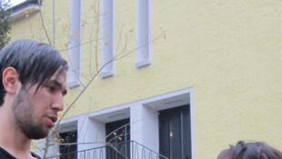 Neo, réfugié en Allemagne, devant l'Eglise de la Sainte Trinité avec une paroissienne allemande.