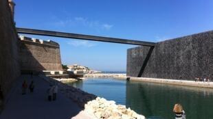 Le Mucem dans le port de Marseille avec vue sur la Méditerranée. La passerelle relie le musée au fort Saint-Jean (à gauche).