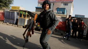 Un policier afghan arrive sur le lieu de l'attentat à Kaboul, le 15 août 2018.