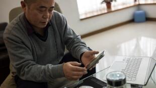 存档图片 黄琦摄于2015年1月22日 Image d'archive: Chinese dissident Huang Qi poses in his apartment in Chengdu, Sichuan province. January 22, 2015.