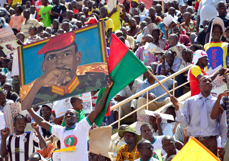 Un membre de l'opposition brandit un portrait de Thomas Sankara lors d'un meeting.