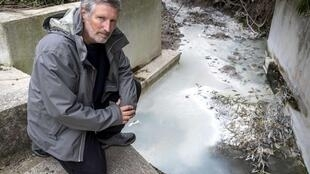 Guy Auge, president of an association defending Salsigne residents, poses by a stream near the defunct Salsigne mine on 4 March, 2019.