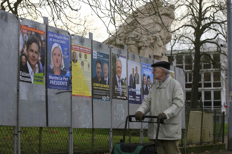 Пенсионер разглядывает предвыборные плакаты кандидатов в Нор-Па-де-Кале на севере Франции