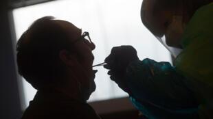 Un voluntario de la la ONG Detente y Ayuda DYA toma una muestra a un pescador antes de salir al mar para realizarle una prueba de detección del coronavirus, el 25 de abril de 2020 en el puerto vasco de Hondarribia (Guipúzcoa), al norte de España