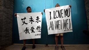 Supporters of Ai Weiwei protest in front of the artist's studio in Beijing on 23 June
