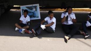 Des enfants cherchent l'ombre d'un camion, lors d'une marche pour la paix à Tegucigalpa, au Honduras, le 5 mai dernier.