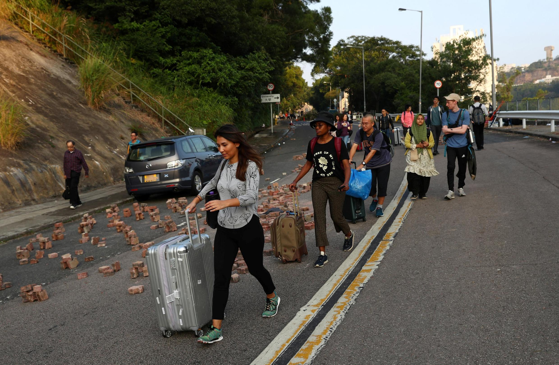 Estudantes internancionais deixam campus da Universidade chinesa de Hong Kong, palco de protestos violentos.