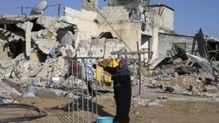 Una mujer palestina cuelga ropa frente a su casa destruida por los bombardeos, el 27 de agosto de 2014.