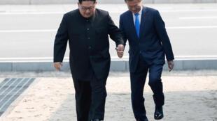 Tổng thống Hàn Quốc Moon Jae In và lãnh đạo Bắc Triều Tiên Kim Jong Un cùng nắm tay bước qua làn ranh định phân giới hai miền, ngày 27/04/2018.