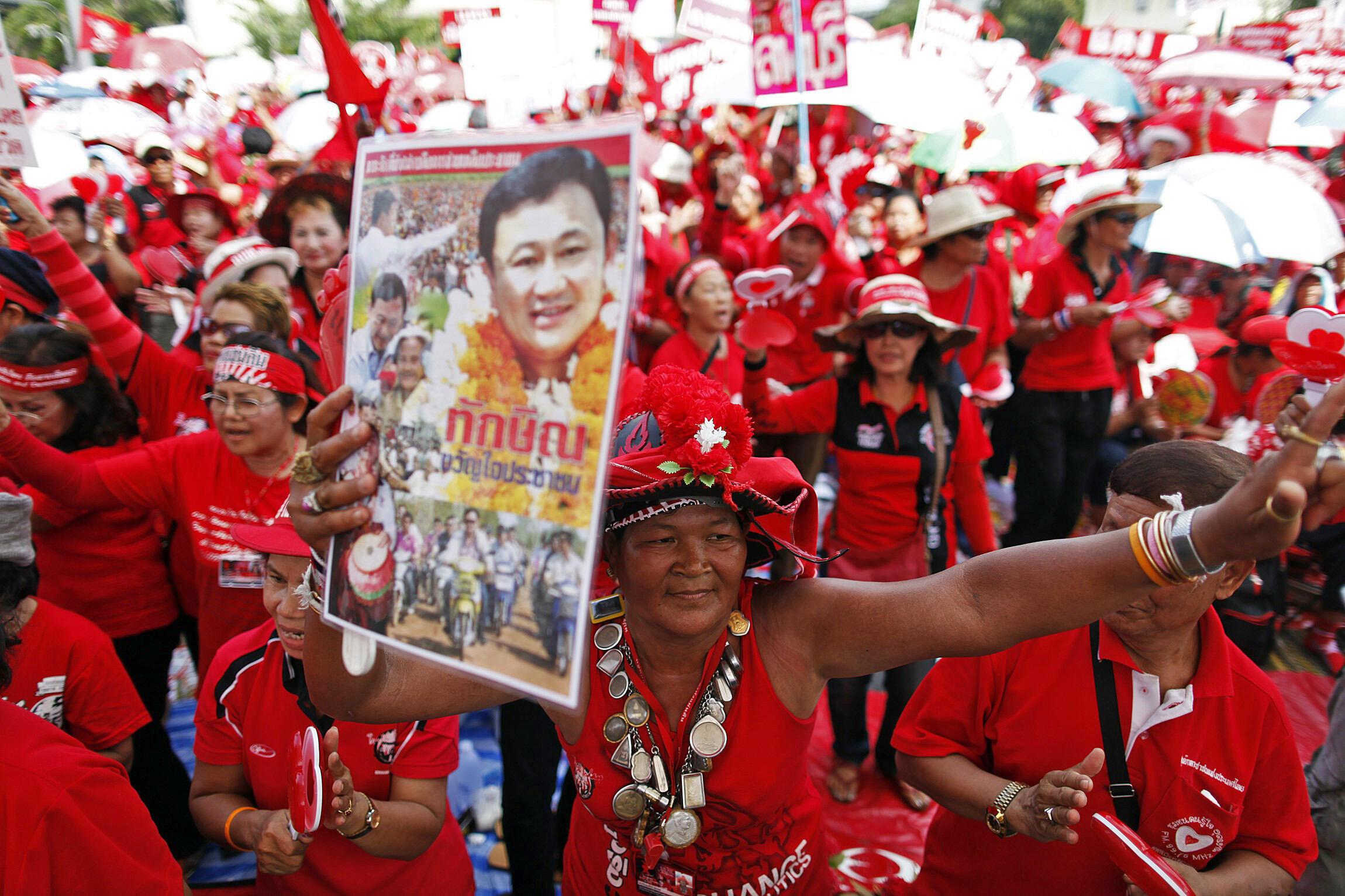 Demonstrators brandish a poster of Thaksin Shinawatra in Bangkok