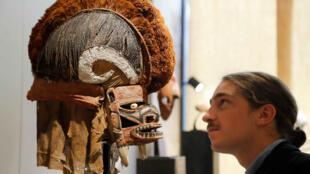 Un visiteur regarde au Parcours des mondes à Paris un masque Tatanua du XIXe siècle, de la Nouvelle-Irlande, en Papouasie Nouvelle-Guinée.