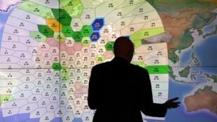 Nhân viên của công ty liên lạc vệ tinh Inmarsat  trước sơ đồ tính toán hành trình của máy bay MH370. Ảnh chụp tại trụ sở của coogn ty ngày 25/3/2014.