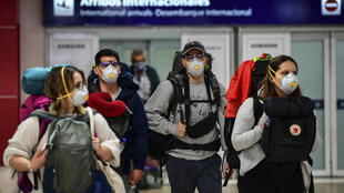 Passengers wearing face masks arrive at Ezeiza International Airport in Buenos Aires