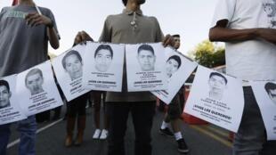 Manifestantes em Guadalajara seguram cartaze com fotografias de estudantes desaparecidos em Iguala
