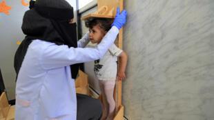 Una técnica sanitaria mide la altura de una niña en la sala de desnutrición del hospital materno-infantil Al Sabin, el 21 de marzo de 2021 en Saná, la capital de Yemen