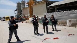 Des membres des forces de sécurité israéliennes se rassemblent devant une usine touchée par une roquette à Ashkelon, le 5 mai 2019.
