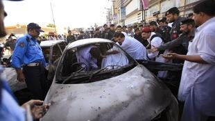 Des secouristes essayent de sortir le corps du chef de la police tué dans un attentat à Peshawar, le 4 août 2010.