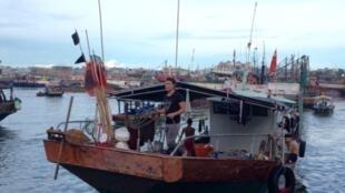 Un bateau de pêche revient du large dans le nouveau port de Sanya.