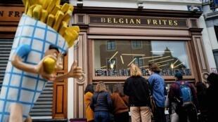 Des gens font la queue devant un vendeur de frites près de la Grand Place au centre de Bruxelles, le 14 mars 2020, en pleine épidémie de Covid-19.