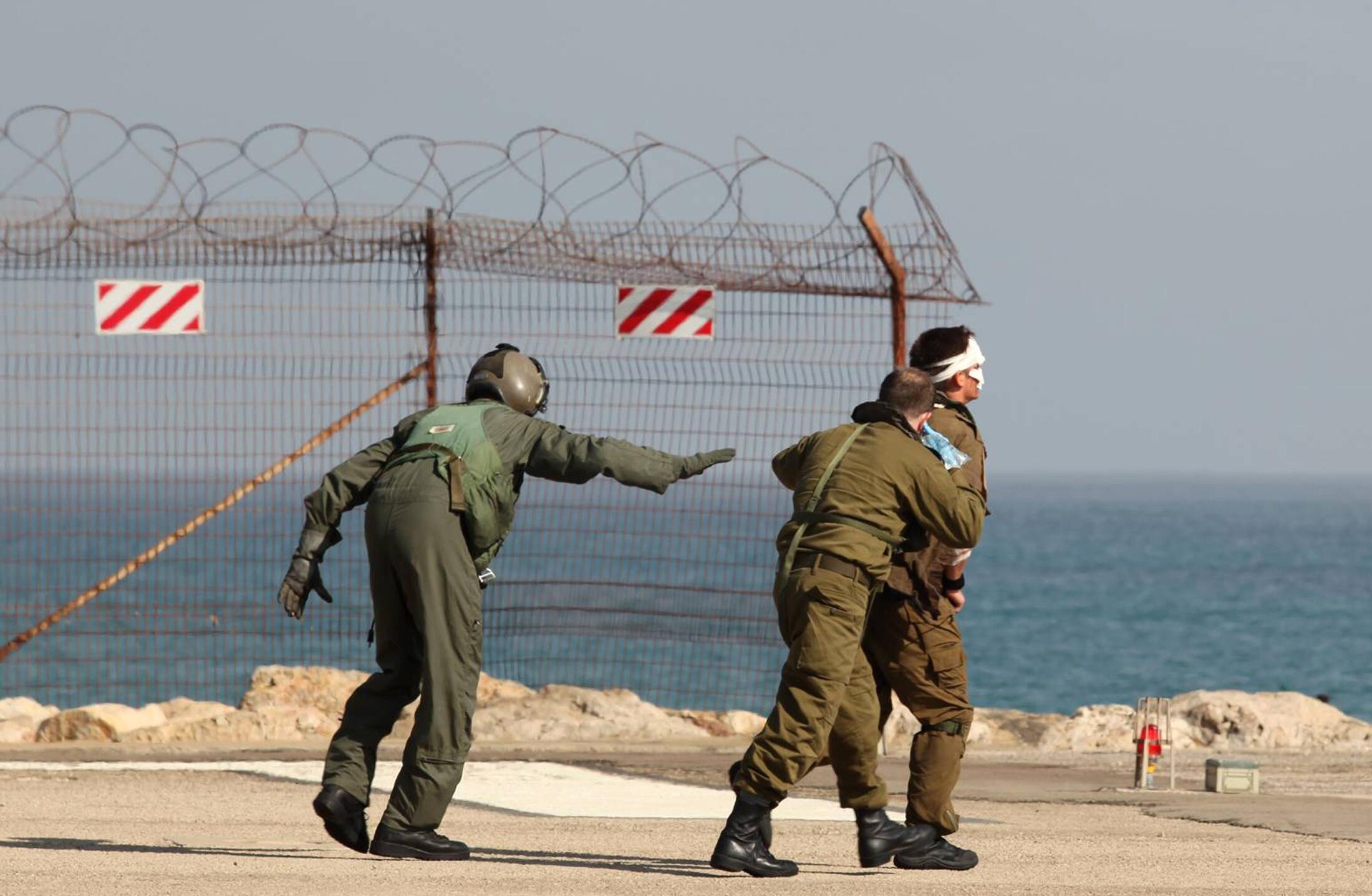 Солдаты израильской армии эвакуируют своего раненого товарища в госпиталь