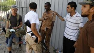 Un homme soupçonné d'avoir été un mercenaire de Kadhafi est arrêté par des ex-insurgés, près de Tripoli, le 28 août 2011.